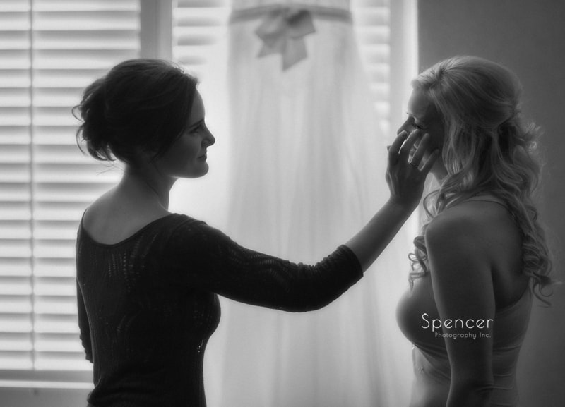 maid of honor wiping tear from brides cheek