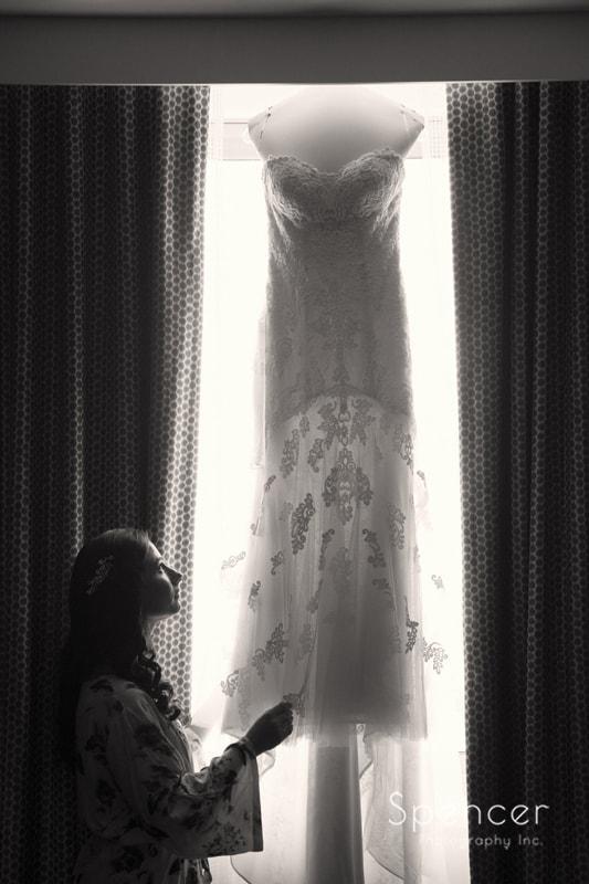 bride grabs her dress which is hanging in window of Westin