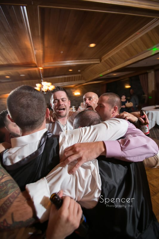 groom dances with friends wedding reception