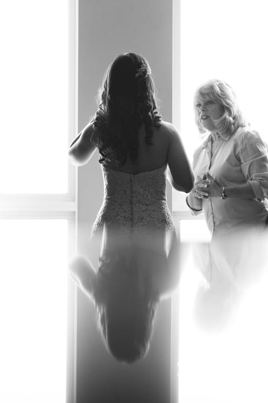 mother of bride helping bride with earrings