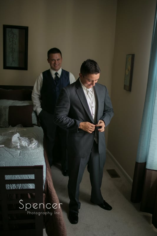 groom buttoning up his tuxedo
