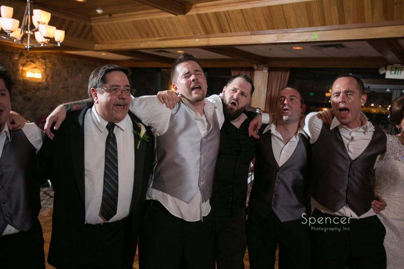groom singing emotionally with friends at his wedding reception