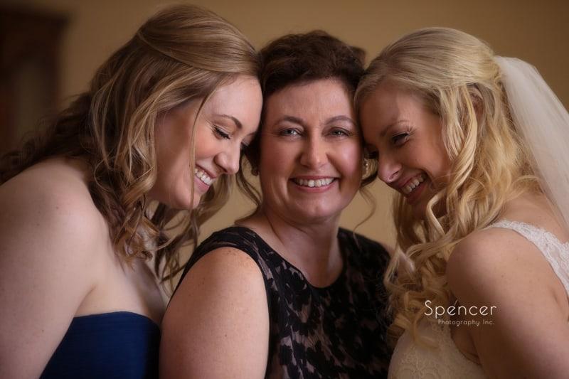 bride and sister hugging mom