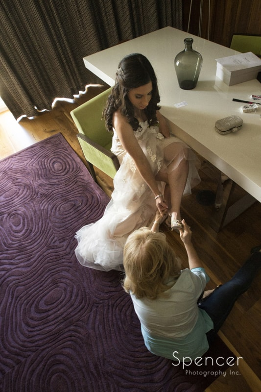 mom helping bride put on her Jimmy Choo's