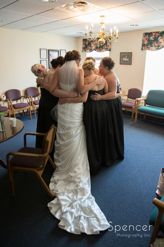 intimate picture of bride with bridesmaids at Church on the Lakes