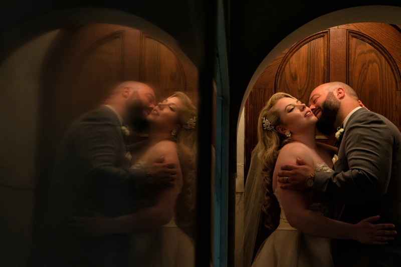 reflection of bride and groom kissing in cleveland church