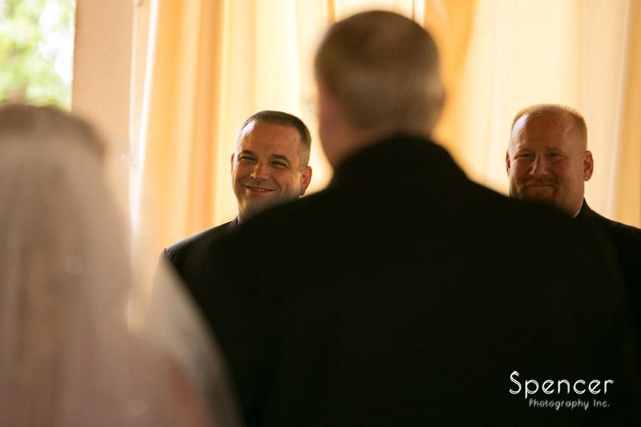 Groom smiling at bride during wedding ceremony at Gervasi Vineyard