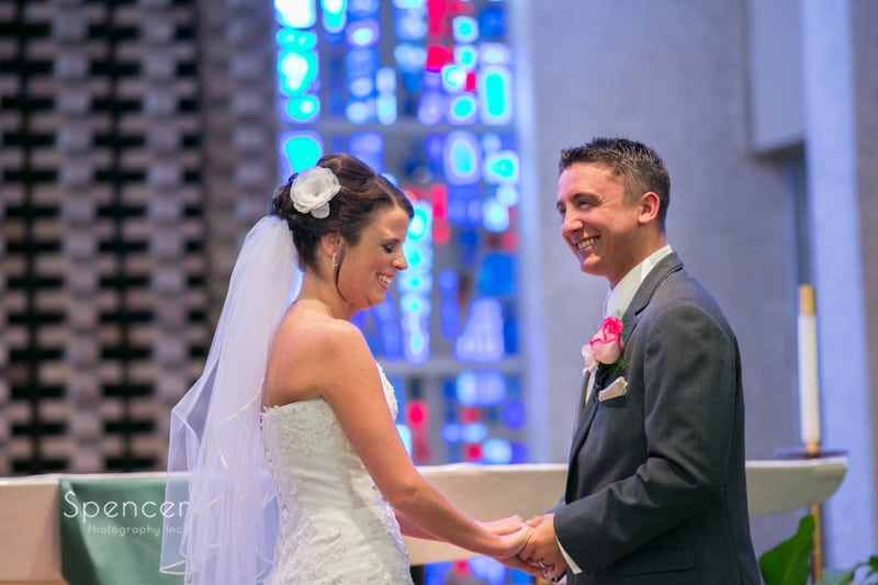 groom and bride laughing on altar of st joseph and john catholic church wedding ceremony