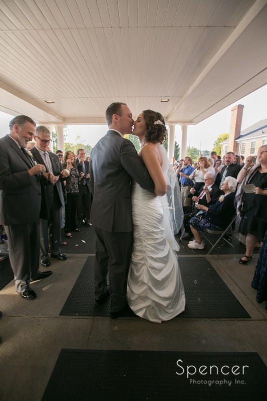 bride and groom kiss while exiting wedding ceremony in Canton