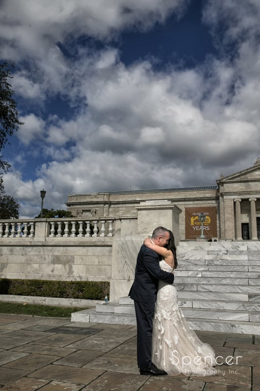 bride and groom hug in front of cleveland museum of art