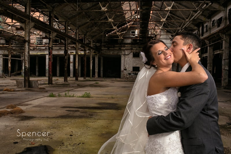 groom kissing bride in artistic wedding picture in warehouse in cleveland