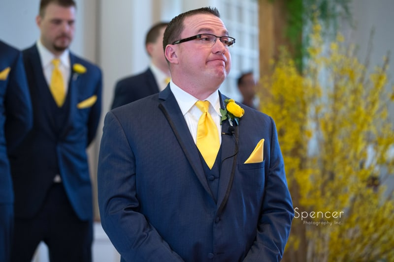 groom watching bride walk down aisle of church in Chagrin Falls
