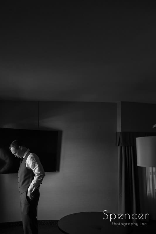black and white picture of groom dressing for wedding in Canton