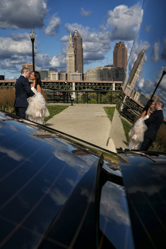 wedding picture with cleveland skyline and reflection in limo window