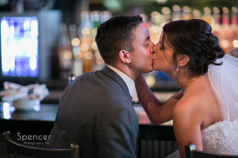 bride and groom kissing in bar in cleveland