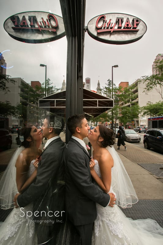 bride and groom kissing outside of city tap in cleveland