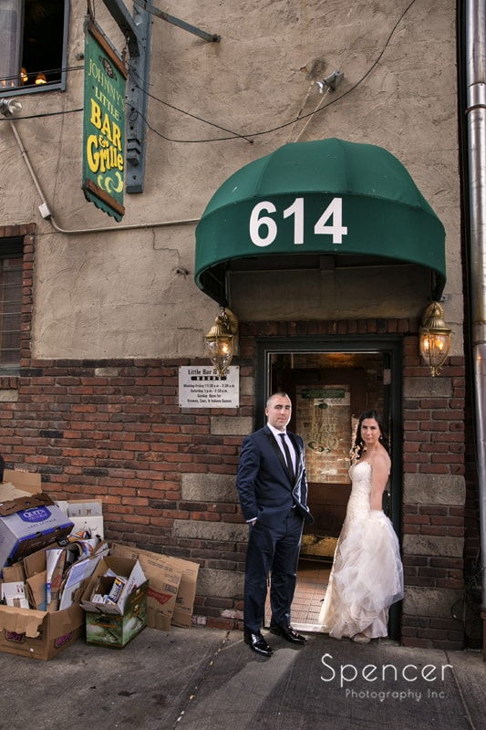 bride and groom pose in front of cleveland bar