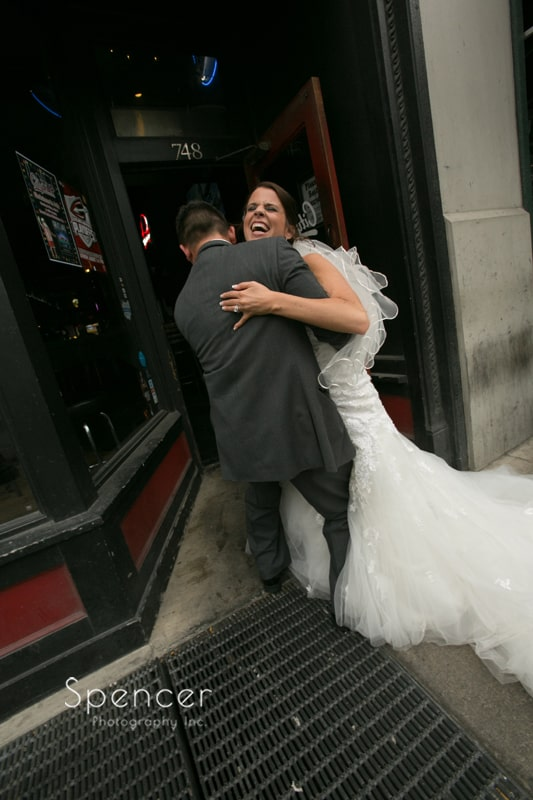 bride and groom cracking up outside bar in cleveland