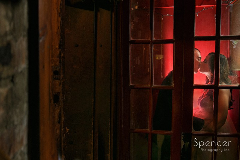 bride and groom kissing in phone booth at Johnnys Cleveland