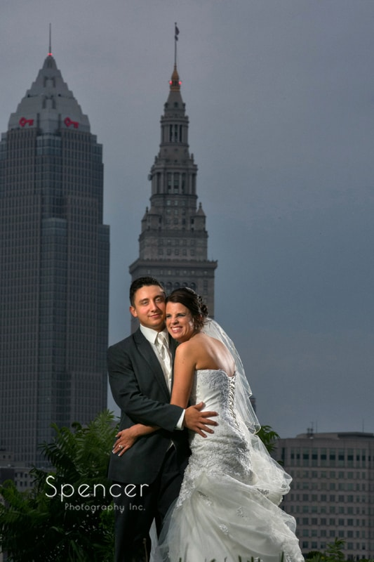 bride and groom pose for wedding picture with cleveland skyline in background