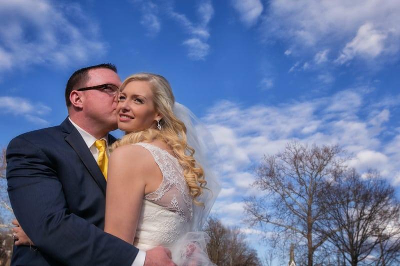 groom kissing brides cheek on bridge in chagrin falls