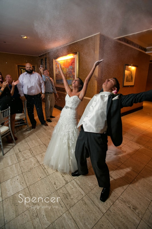 bride and groom celebrate their entrance to their reception at st clair ballroom