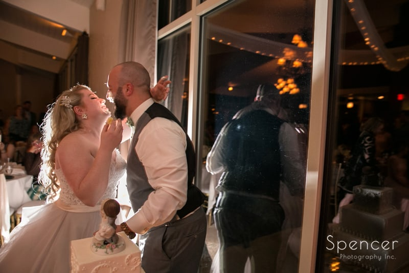 bride kisses groom after eating wedding cake at wedding reception at tanglewood