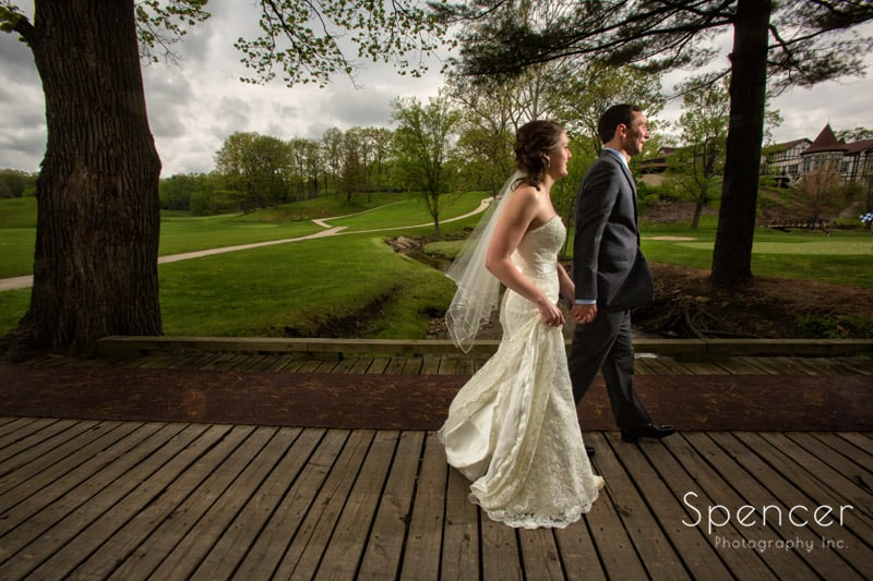 bride and groom walking to get pictures at Mayfield Country Club