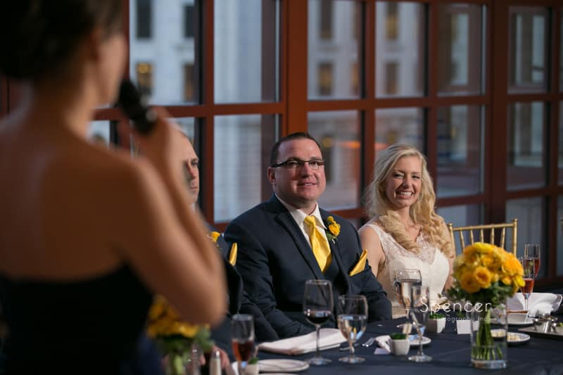 maid of honor looking at bride and groom a their wedding reception during speech