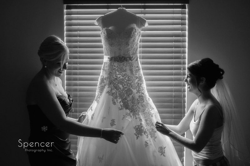 bride and maid of honor handling wedding dress