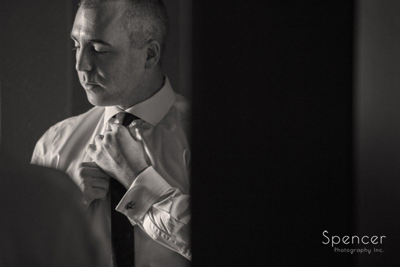 Groom adjusts his tie in preparation for his wedding day at Westin Cleveland