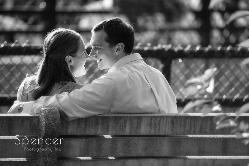 couple sitting on bench in chagrin falls for their engagement photography