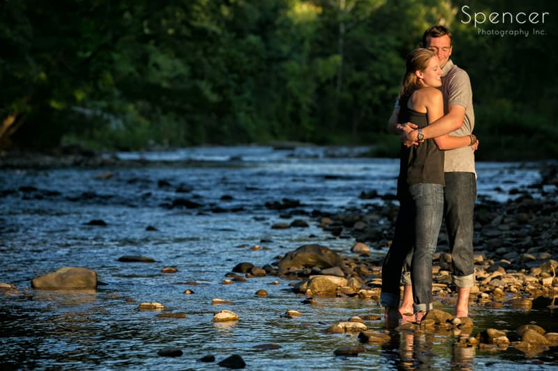 couple standing in the chagrin river hugging