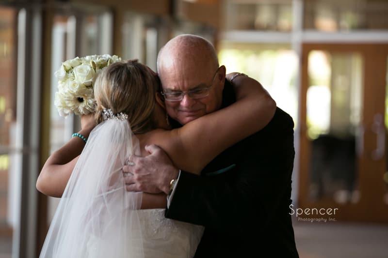 bride hugs her parents before wedding at St. John Vianney