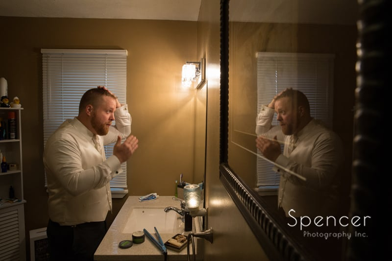 groom fixing hair before wedding in mentor