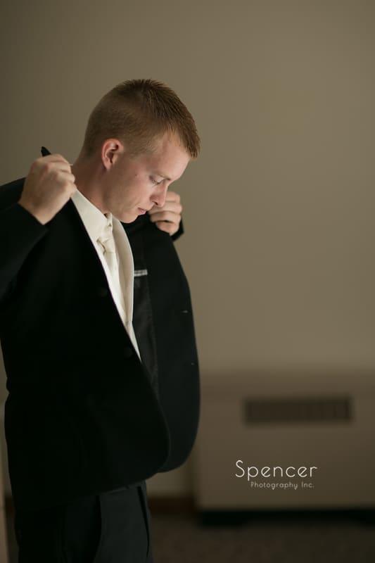 groom putting on his tux jacket