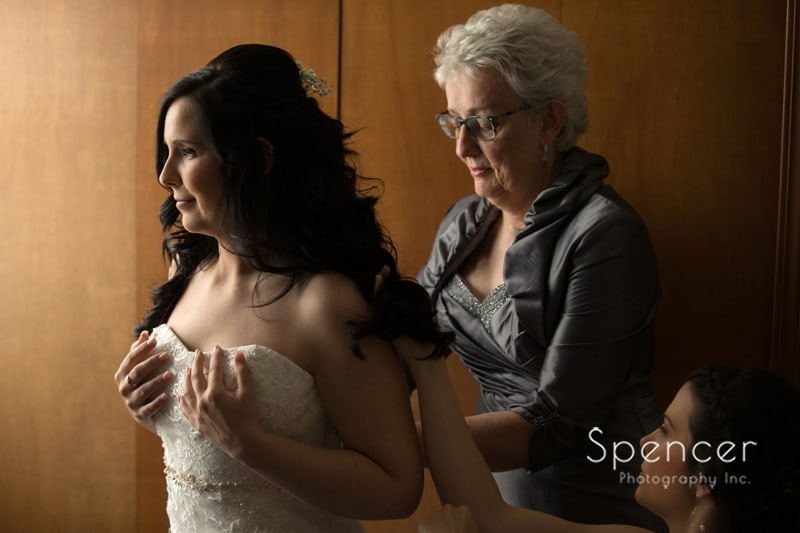 mom helping bride put on wedding dress