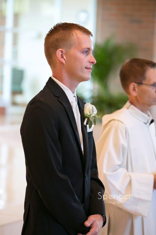 groom watching bride walking down aisle at Mentor church