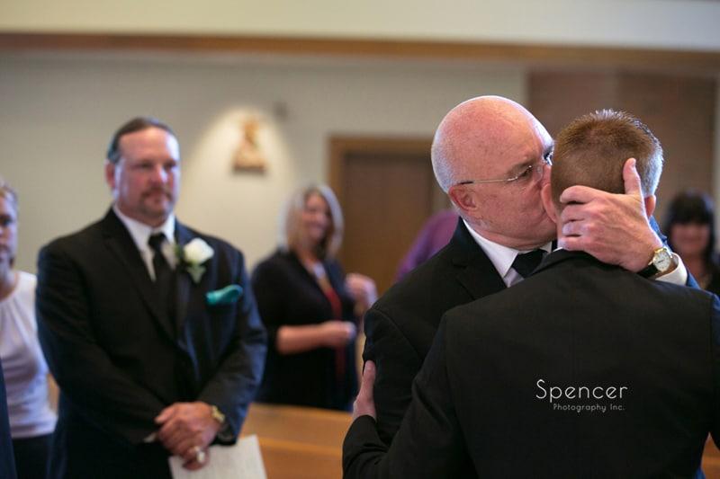 brides dad hugging groom at ceremony