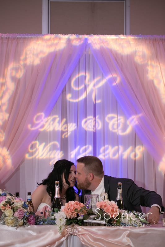 bride and groom kiss in front of Burning River Entertainment gobo