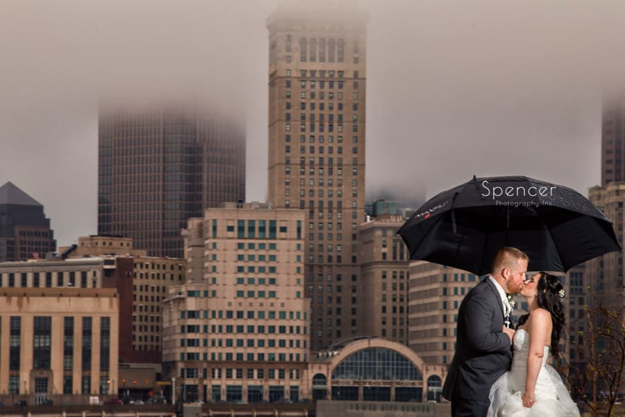 picture of bride and groom kissing with cleveland in background