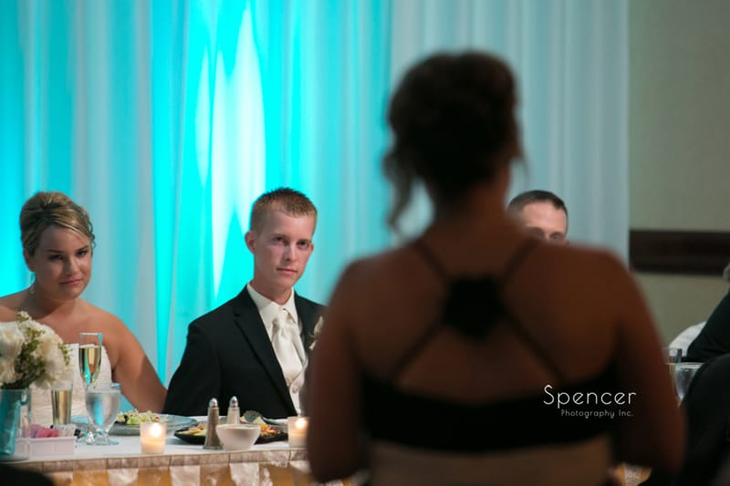 bride and groom listening to maid of honor reception speech