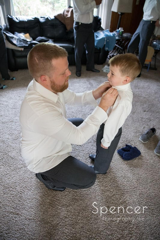 groom helping son get dressed for wedding day in Mentor