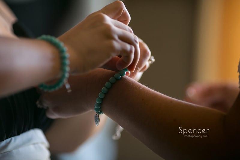 brides mom putting on bracelet