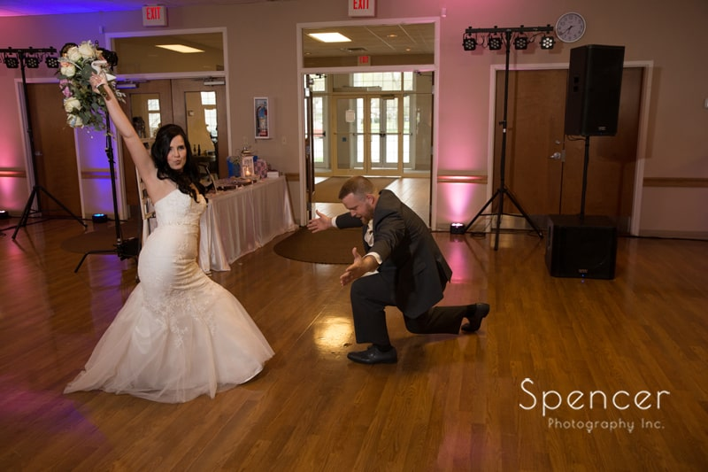 groom bowing to bride at their wedding reception in Perry Ohioi