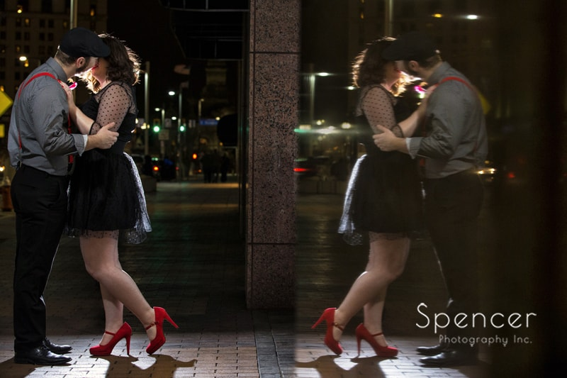 couple kissing with reflection for engagement pictures in Cleveland