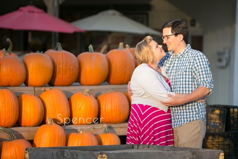 fall engagement picture in akron with pumpkins