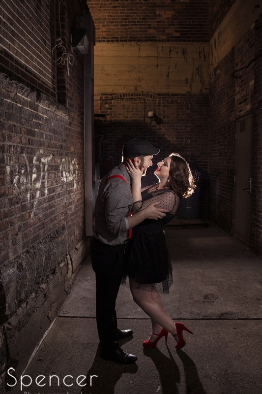 full length picture of couple kissing during engagment session in downtown Cleveland