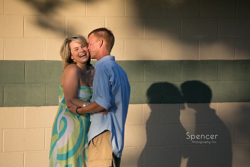 woman laughing while man kisses her during engagement session on lake erie