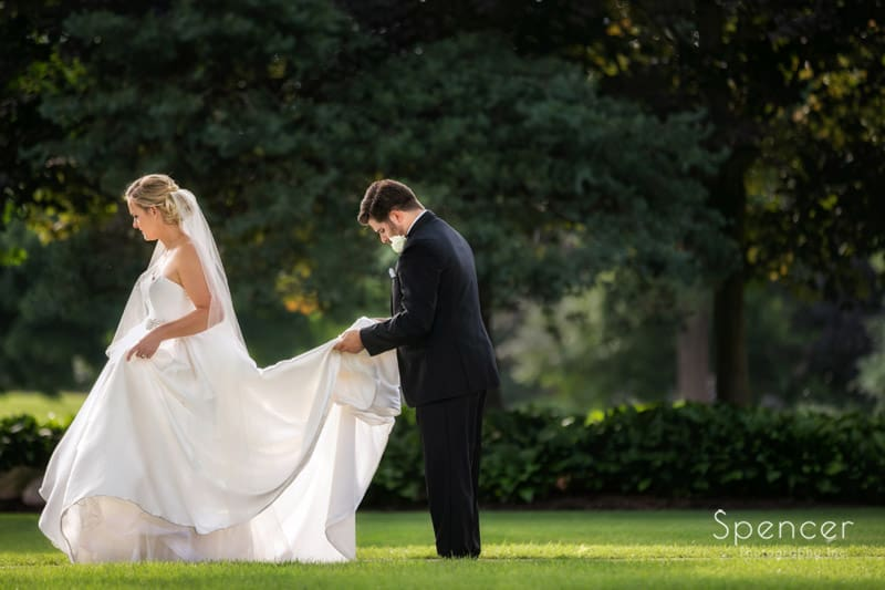 groom helping bride wedding wedding dress at Firestone Country Club wedding reception